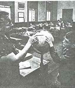 Teacher, Mrs. Mary Clark, uses the globe to explain geography.