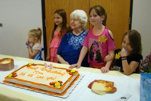 Some of Luella's grandchildren look over her 90th birthday cake.