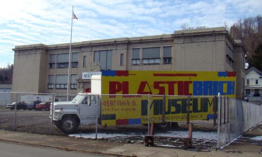 Plastic Brick Museum Sign in front of building.