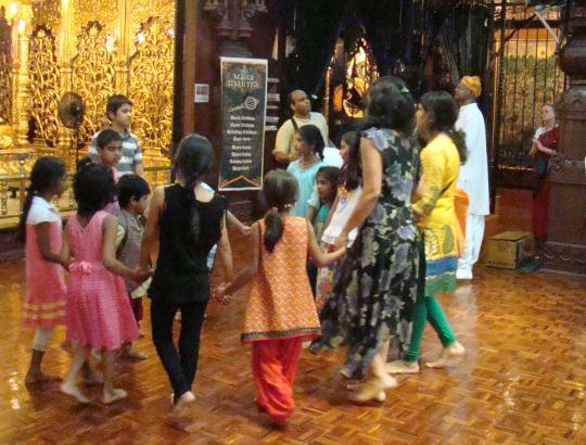 Children chant and dance before the altar.