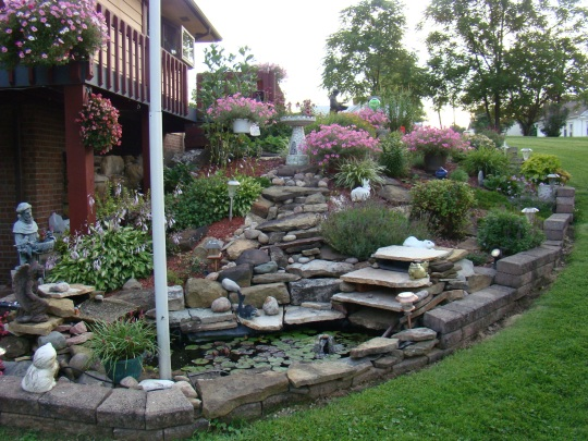 Beautiful flowers and stones surround a small pond in a neighbor's yard.